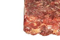 Djupfryst kvarter av nötkött på en vit bakgrund arkivfoto