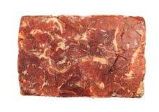 Djupfryst kvarter av nötkött på en vit bakgrund royaltyfria bilder