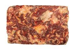 Djupfryst kvarter av nötkött på en vit bakgrund arkivbilder