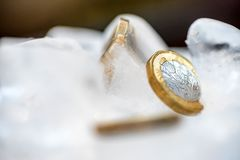 Djupfryst ny britt ett pundmynt upp nära makro inom iskuber Arkivbild