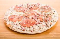 Djupfryst peperonipizza på den Wood skärbrädan royaltyfria foton