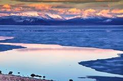 Djupfryst sjö med berg under solnedgång Arkivbilder