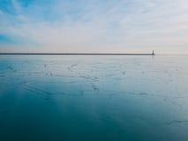 Djupfryst sjö med fyren Arkivbilder