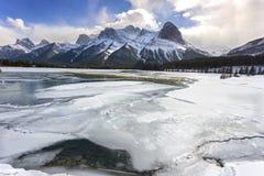 Djupfryst sjö och avlägsen Snowcapped kanadensare Rocky Mountains Canmore Alberta fotografering för bildbyråer