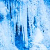 Djupfryst vattenfall av blåa istappar Arkivbilder