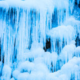 Djupfryst vattenfall av blåa istappar Arkivbild