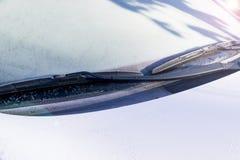 Djupfryst vindrutetorkare och exponeringsglas på bilen Djupfryst vindruta Djupfryst vit bil i vinter Is på främre fönster av en b Royaltyfri Bild
