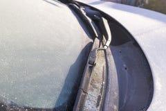 Djupfryst vindrutetorkare och exponeringsglas på bilen Djupfryst vindruta Djupfryst vit bil i vinter Is på främre fönster av en b Royaltyfria Foton