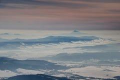 Djupfryst vinterlandskap med bergkanter under orange himmel royaltyfri bild