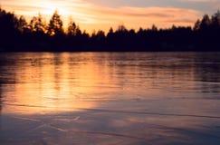 Djupfryst vintersjö på solnedgången Arkivfoto