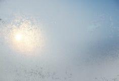 Djupfryst vitt fönster som täckas med frost i den mönstrade vintern Royaltyfri Foto
