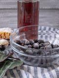 Djupfrysta bär i en exponeringsglasbunke, ett exponeringsglas av röd fruktsaft arkivfoton
