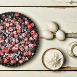 Djupfrysta bär, mjöl, ägg och mjölkar på en lantlig vit tabell stekheta ingredienser Arkivbild