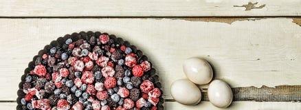 Djupfrysta bär, mjöl, ägg och mjölkar på en lantlig vit tabell stekheta ingredienser Arkivfoton