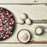Djupfrysta bär, mjöl, ägg och mjölkar på en lantlig vit tabell stekheta ingredienser Royaltyfri Fotografi