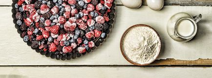 Djupfrysta bär, mjöl, ägg och mjölkar på en lantlig vit tabell stekheta ingredienser Royaltyfria Bilder