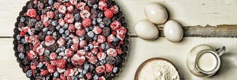 Djupfrysta bär, mjöl, ägg och mjölkar på en lantlig vit tabell stekheta ingredienser Fotografering för Bildbyråer