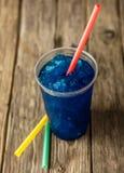 Djupfrysta blåa Slushie i plast- kopp med sugrör royaltyfri foto
