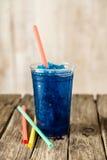 Djupfrysta blåa Slushie i plast- kopp med sugrör royaltyfria bilder