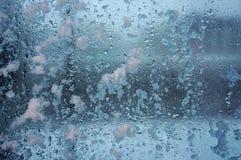 Djupfrysta droppar och snö på frostat exponeringsglas Fotografering för Bildbyråer