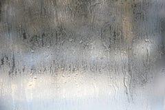 Djupfrysta droppar på frostat exponeringsglas Vinter texturerad bakgrund Arkivbilder