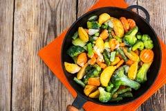 Djupfrysta grönsaker för att steka i en panna arkivfoto