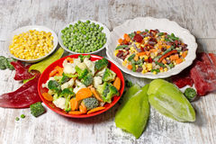 Djupfrysta grönsaker i platta och bunke, fryste grönsaker behåller alla näringsämnar Fotografering för Bildbyråer