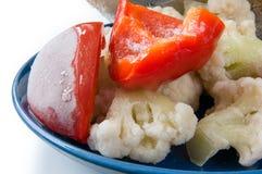 Djupfrysta grönsaker på den blåa plattacloseupen Royaltyfri Foto