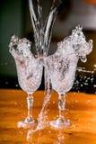 Djupfrysta härliga vinexponeringsglas för färgstänk itu på en tabell mot en mörk bakgrund royaltyfri foto