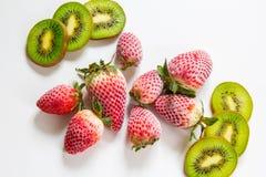 Djupfrysta jordgubbar och klippt kiwi på den vita tabellen royaltyfria foton
