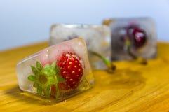 Djupfrysta körsbär och jordgubbar i ce Arkivfoton