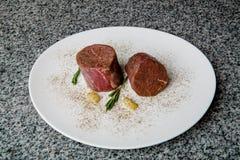 Djupfrysta nötköttbiffar på en vit platta royaltyfria foton