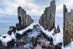 Djupfrysta trävågbrytare fodrar till plattformen för torpeden för världskrig II på Östersjön Arkivfoton