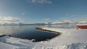 Djupt öppet fjordlandskap med väldig snöig bergskedja i bakgrunden stock video