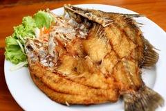 Djupt stekt fisk med grönsaker på den vita maträtten Royaltyfria Bilder