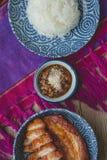 Djupt stekt griskött med klibbiga ris på thai tyg och gammalt trä, Arkivfoto
