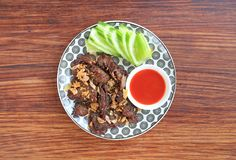 Djupt stekt nötkött som tjänas som med den skivade gurkan och söt chilisås på träbrädebakgrund fotografering för bildbyråer