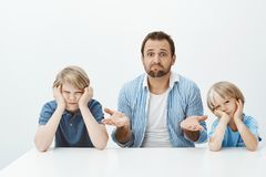 Dlaczego synowie są szalenie Portret nieświadomy nerwowy teścia obsiadanie z dwa ślicznymi chłopiec przy stołem, wzruszający rami fotografia stock