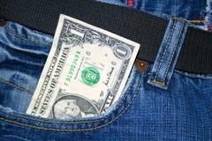 Dólar de papel en un bolsillo de los pantalones vaqueros Foto de archivo