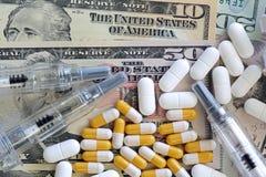 Dólares de EE. UU. con las píldoras y la jeringuilla Imagen de archivo libre de regalías
