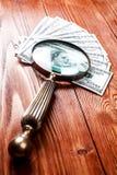 Dólares e lupa Fotografia de Stock