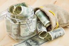 Dólares en el tarro y el bolso de cristal del dinero Fotografía de archivo libre de regalías