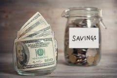 Dólares y monedas en tarro con la etiqueta del ahorro Fotografía de archivo libre de regalías