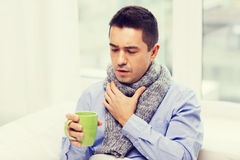 Dåligt man med influensa som dricker te och hemma hostar Arkivbild