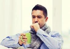 Dåligt man med influensa som dricker te och hemma hostar Fotografering för Bildbyråer