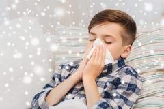 Dåligt pojke som ligger i säng och hemma blåser hans näsa Arkivfoto