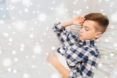 Dåligt pojke som ligger i säng och lider från huvudvärk Arkivbild
