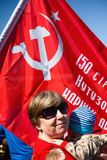 Grandmother and grandsonon the background of the red flag in the Immortal Regiment Stock Image