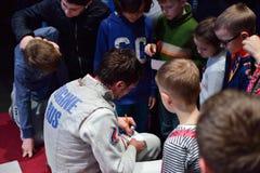 Dmitry Rigin ger autografer till barn Arkivbild