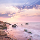 Dämmerungssonnenaufganglandschaft über schöner felsiger Küstenlinie im Meer Lizenzfreies Stockfoto